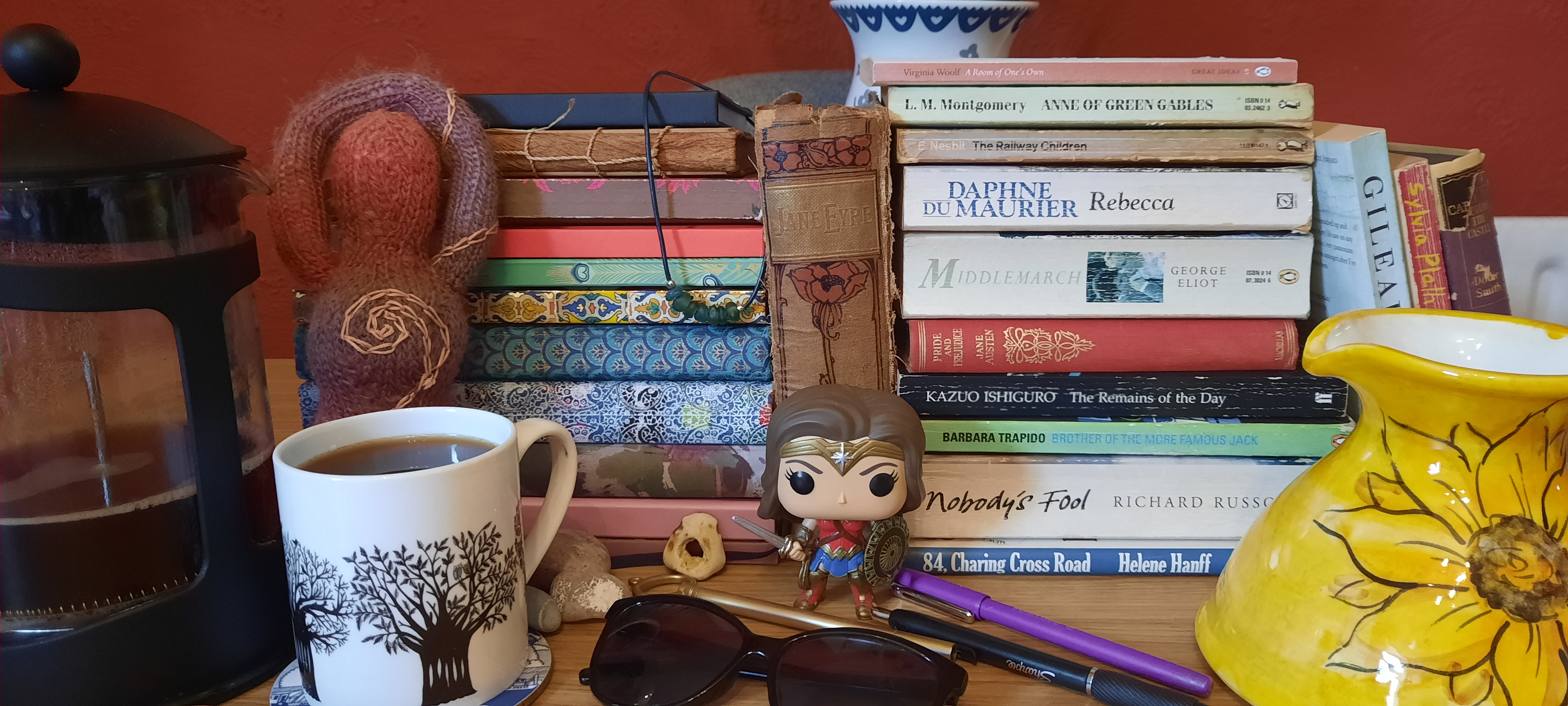 A picture of a pile of notebooks, next to a stack of published books, a jug with sunflowers on it, a pot of coffee, some pens, pebbles and sunflowers and a figure of Wonder Woman